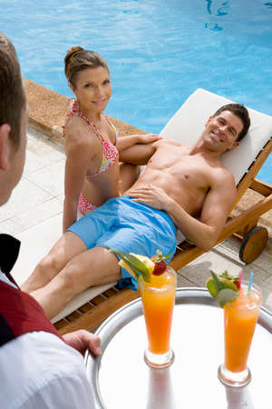 lounge chair: Waiter serving tropical drinks to couple on lounge chair at poolside LANG_EVOIMAGES