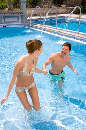waist deep: Smiling couple holding hands in swimming pool LANG_EVOIMAGES