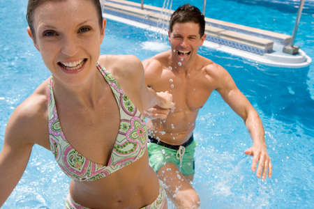 bare waist: Smiling couple holding hands in swimming pool LANG_EVOIMAGES