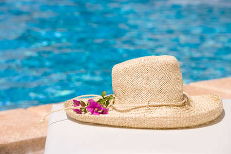 lounge chair: Hat with flower on lounge chair at poolside