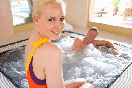 hot tub: Smiling couple in hot tub LANG_EVOIMAGES