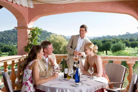welldressed: Well-dressed couples drinking wine at table on restaurant balcony