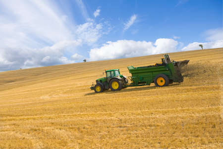 farm landscape: Tractor spreading fertilizer in sunny rural field