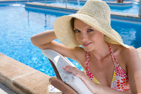 lounge chair: Smiling woman wearing sun hat and laying on lounge chair at poolside LANG_EVOIMAGES