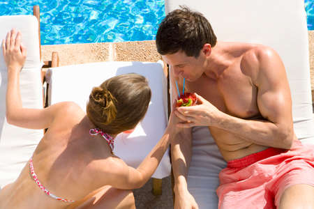 bare waist: Couple sharing tropical drink on lounge chairs at poolside LANG_EVOIMAGES