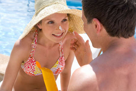 bare waist: Man applying sunscreen to womanճ nose at poolside