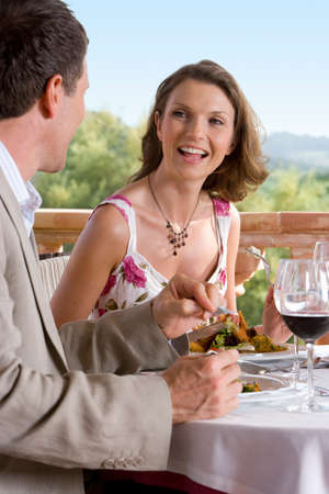 couple dining: Well-dressed couple dining at table on restaurant balcony