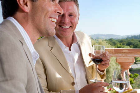 welldressed: Well-dressed men drinking wine on restaurant balcony