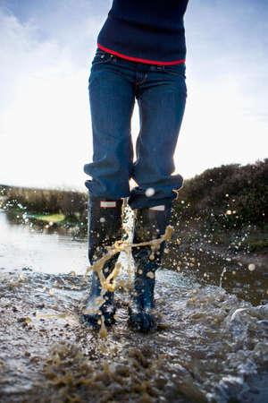 wellingtons: Woman in wellingtons splashing in water