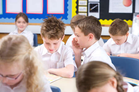confiding: School boys whispering secrets in classroom