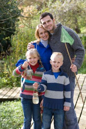 specimen: Family with bug net and specimen jars outdoors