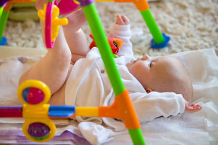 changing diaper: Baby laying on floor playing with toy