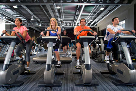 health club: Men and women riding exercise bikes in health club