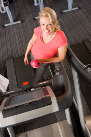health club: Portrait of smiling senior woman with water bottle leaning on treadmill in health club LANG_EVOIMAGES