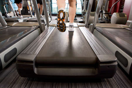 exercise equipment: Legs of man running on treadmill in health club