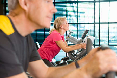 health club: Man and woman riding exercise bikes in health club LANG_EVOIMAGES
