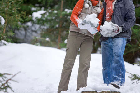 palle di neve: Couple holding large snowballs in woods