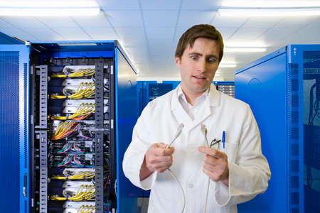 it technician: Confused IT technician looking at LAN cable in network server room LANG_EVOIMAGES