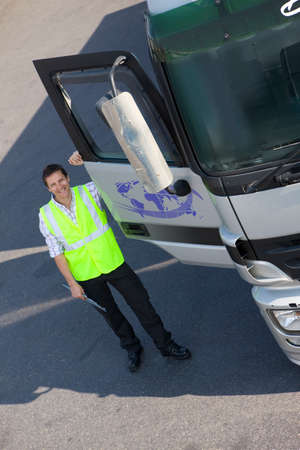 leaning on the truck: Truck driver standing near open door of semi-truck
