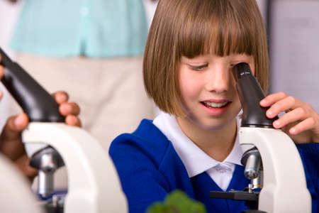 niños en la escuela: Los escolares que buscan en los microscopios en laboratorio aula