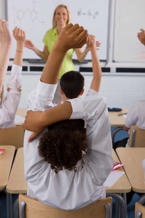 answering: Students answering teachers questions in classroom