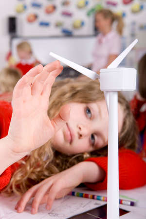 carbon neutral: Serious school girl spinning model wind turbine in classroom