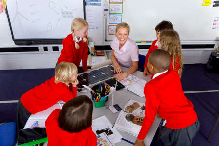 Teacher and school children looking at solar panel and model wind turbines LANG_EVOIMAGES