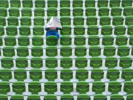 concealing: Senior man sleeping newspapers in green stadium seats LANG_EVOIMAGES