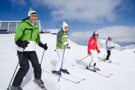 SKI: Family of skiers skiing downhill on ski slope LANG_EVOIMAGES