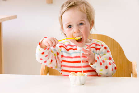 high chair: Baby girl in high chair eating banana slices LANG_EVOIMAGES