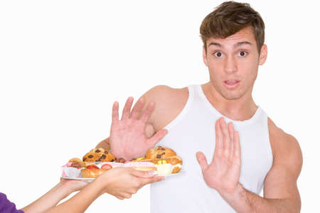 refusing: Man refusing plate of desserts LANG_EVOIMAGES