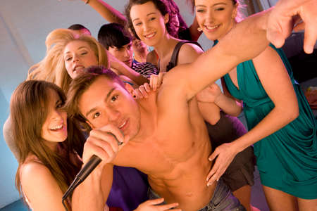 bare chested: Women dancing behind bare chested man singing into microphone
