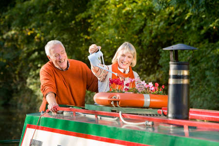 away from it all: Couple watering potted flowers on boat