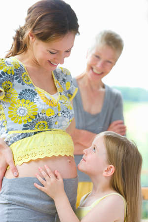 expectant arms: Daughter touching mothers pregnant stomach as grandmother watches LANG_EVOIMAGES