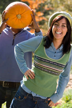 concealing: Playful couple with autumn pumpkin LANG_EVOIMAGES