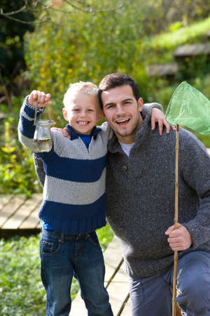 specimen: Father and son holding bug net and specimen jar outdoors