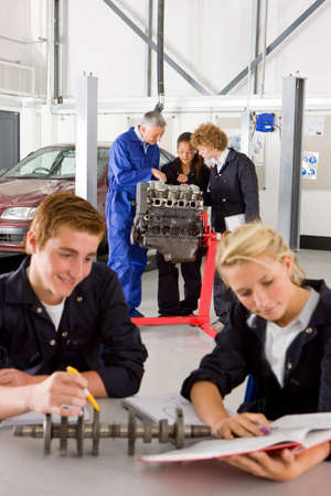 auto mechanic: Students with auto part studying automotive trade in vocational school