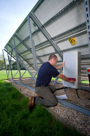 carbon neutral: Technician inspecting control panel on large solar panel LANG_EVOIMAGES