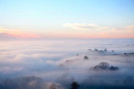 vastness: Sunrise and blue sky over fog covered landscape