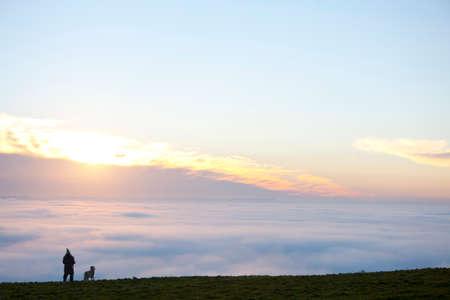 mujer mirando el horizonte: Persona y perro en la colina de ver la salida del sol y la niebla cubre paisaje LANG_EVOIMAGES