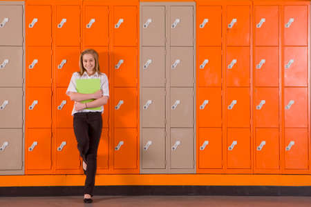 preadolescent: Student leaning on school lockers LANG_EVOIMAGES