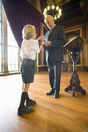 lectern: School boy (5-7) receiving trophy from man at lectern in hall, low angle view