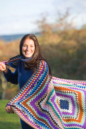 hair wrapped up: Smiling woman wrapped in blanket outdoors