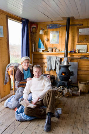 wood burning stove: Couple relaxing in living room with wood burning stove