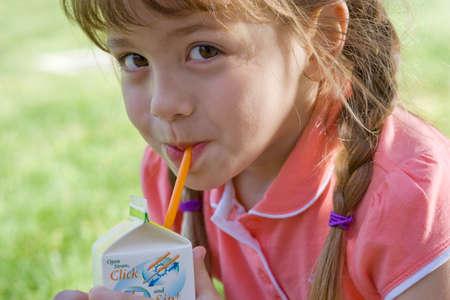 alimentos y bebidas: Primer plano de ni�a de beber jugo de caja