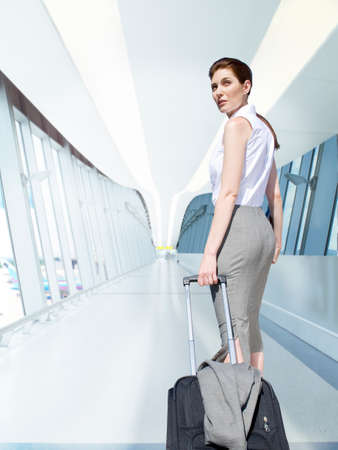 concourse: Businesswoman pulling rolling luggage in airport concourse