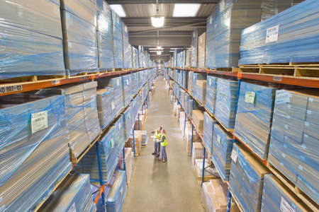 people working together: Warehouse workers looking up at cardboard boxes on shelves