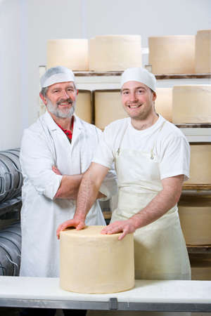 binding: Portrait of smiling cheese makers binding new farmhouse cheddar cheese wheel with cheesecloth