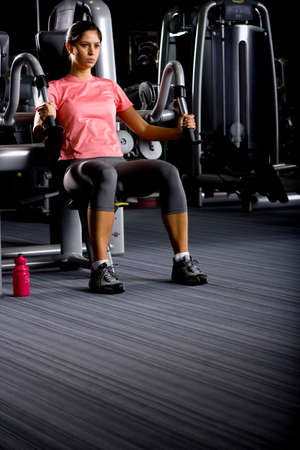 exertion: Woman weight lifting with exercise equipment in health club