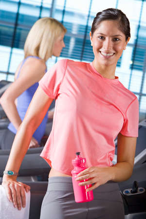 health club: Portrait of smiling woman holding water bottle on treadmill in health club LANG_EVOIMAGES